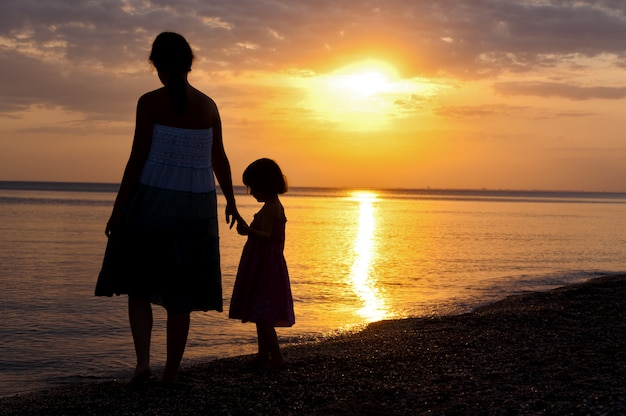 Мать и ребенок силуэты на пляж заката.