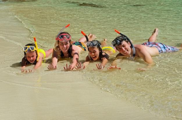 シュノーケリングと熱帯のビーチでの休暇を楽しんで幸せな家族