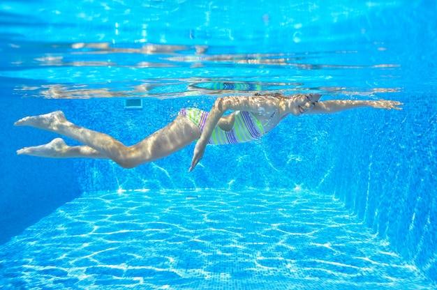 幸せなアクティブな子供がプールで水中を泳ぐ