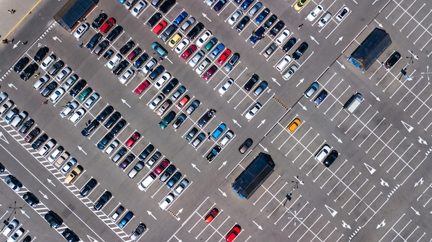 Воздушный беспилотный вид на стоянку с множеством автомобилей сверху, городской транспорт и городская концепция