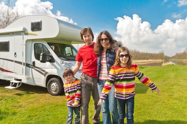 Семейный отдых, путешествие на автофургоне с детьми, счастливые родители с детьми в отпуске в автодоме