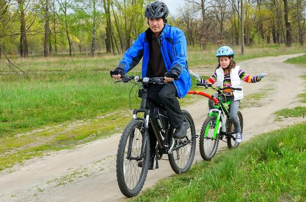 Счастливый отец и ребенок на велосипедах, семья на велосипеде на открытом воздухе
