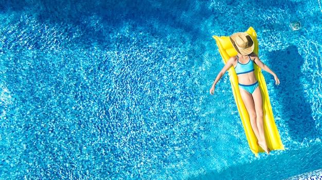 スイミングプールでリラックスした女の子、子供は膨脹可能なマットレスで泳ぐし、家族での休暇に水で楽しんでいます