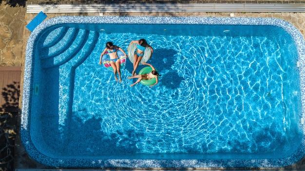 上からスイミングプール空中ドローンビューで家族、幸せな母と子供はインフレータブルリングドーナツで泳ぐし、家族での休暇、リゾートで熱帯の休日に水で楽しい