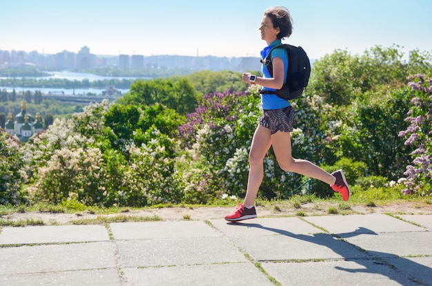 バックパック、市朝ラン通勤とフィットネスの概念、キエフ、ウクライナで動作するように女性ランナー実行通勤