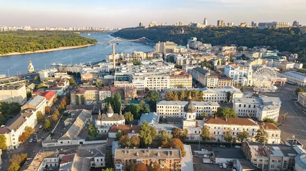 上からキエフの街並み、ドニエプル川、ポドル歴史地区のスカイライン、観覧車のあるコントラクトヴァ広場、キエフ、ウクライナの都市の空中のトップビュー