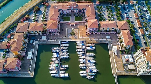 Вид с воздуха на пристань для яхт с лодки и яхты на порт современного жилого района сверху