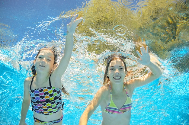 Дети плавают под водой в бассейне, счастливые активные девочки веселятся под водой, дети занимаются фитнесом и спортом на активном семейном отдыхе.