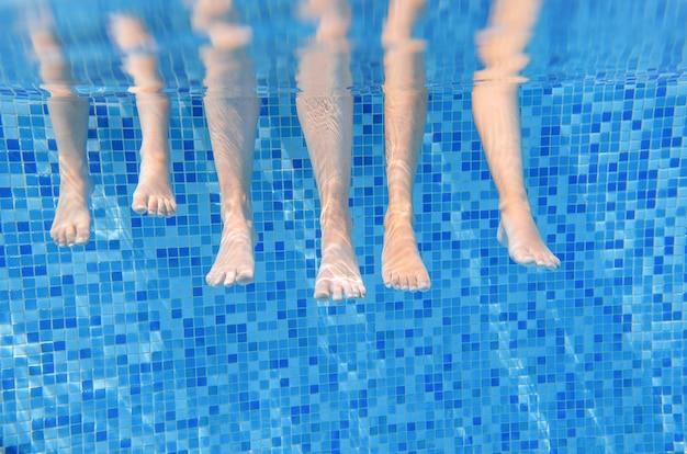 スイミングプールで水中の家族の足、水面白い概念、スポーツ、子供との休暇の下で子供と泳ぐ