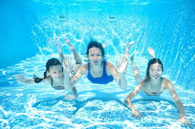 家族は水中のプールで泳ぐ、アクティブな母親と子供たちはリゾートで夏休みに子供と一緒に水、フィットネス、スポーツの下で楽しい