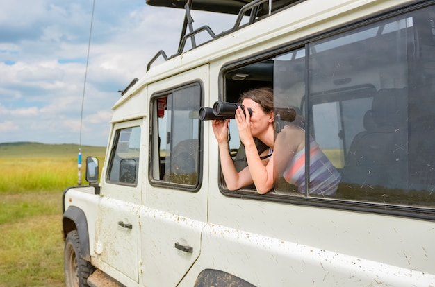 アフリカのサファリで女性観光客、ケニアで旅行、双眼鏡でサバンナの野生生物を見て