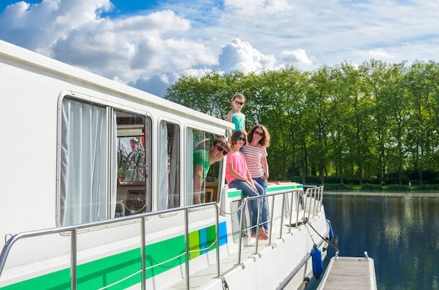 Семейный отдых, летние каникулы на лодке на барже в канале, счастливые дети и родители веселятся в речном круизе на плавучем доме во франции