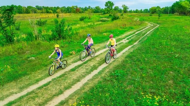 上から自転車屋外空撮で家族サイクリング、子供と幸せなアクティブな母親が楽しい、家族のスポーツとフィットネス