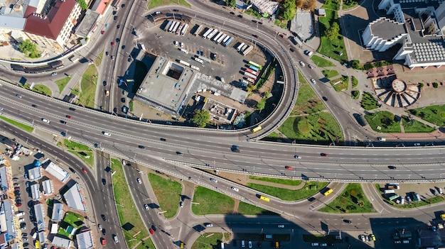 上からの道路のジャンクション、自動車交通および多くの車の込み合い、交通機関の概念の空中のトップビュー