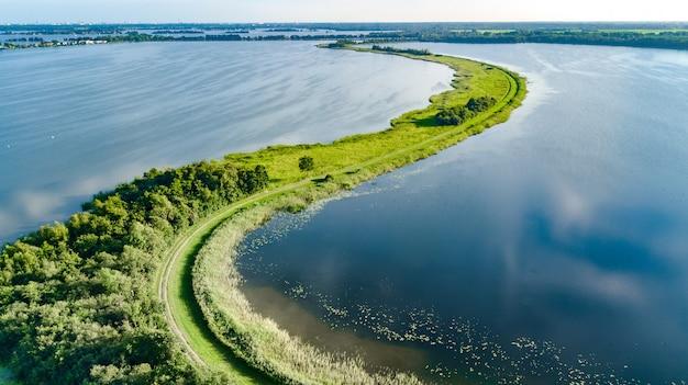 Воздушный беспилотный вид пути на плотине в польдерной воде сверху, ландшафт и природа северной голландии, нидерланды