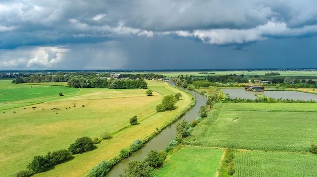緑の野原と上から運河近くの農家の空中ドローンビュー、典型的なオランダの風景、オランダ、オランダ
