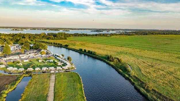 運河、干拓地の水、緑の野原、オランダ、オランダの上から農家の典型的なオランダの風景の空中ドローンビュー