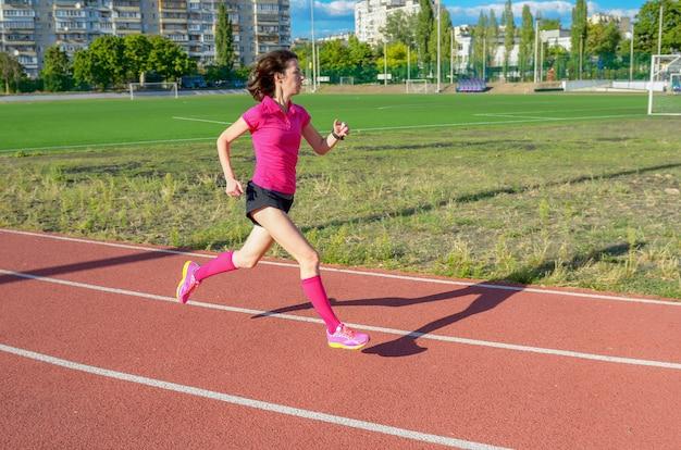 Счастливая активная женщина работает на треке, спринте и работает на стадионе, спорт и фитнес в городе, городской фон