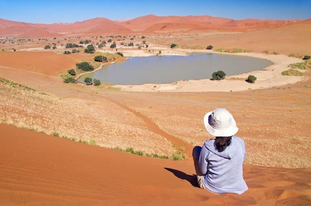 Женщина-путешественница в африке, отдых в намибии, глядя на красивый пейзаж пустыни намиб