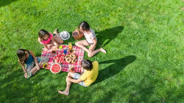 公園でピクニックを持つ子供、庭の草の上に座って屋外で健康的な食事を食べる子供を持つ親と幸せな家族