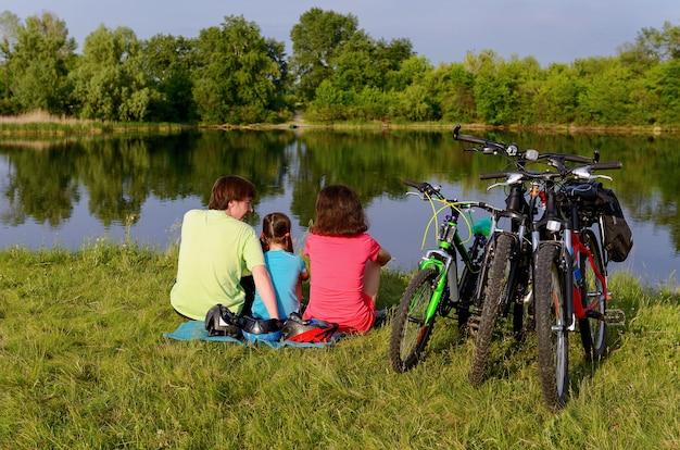 Семейная поездка на велосипеде на открытом воздухе, активные родители и ребенок на велосипеде и отдых у красивой реки