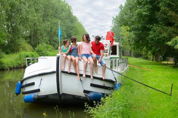 Семейный отдых, путешествие на лодке на барже по каналу, счастливые дети веселятся в речном круизе в плавучем доме