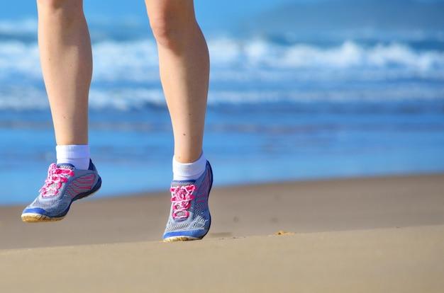 フィットネス、ビーチ、海、健康的なライフスタイル、スポーツコンセプトの近くの砂の上をジョギングシューズで女性ランナーの足で実行