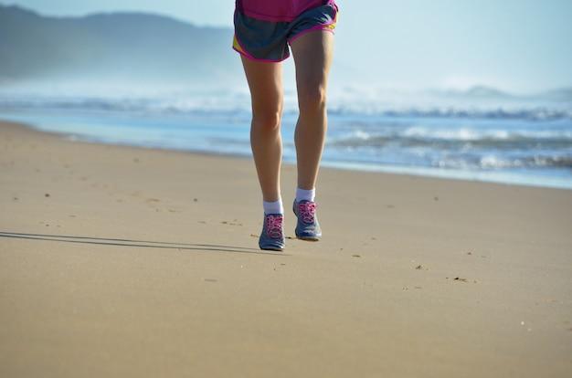 Фитнес и бег на пляже, ноги бегуна женщины в обуви, бег на песке у моря, здоровый образ жизни и концепция спорта