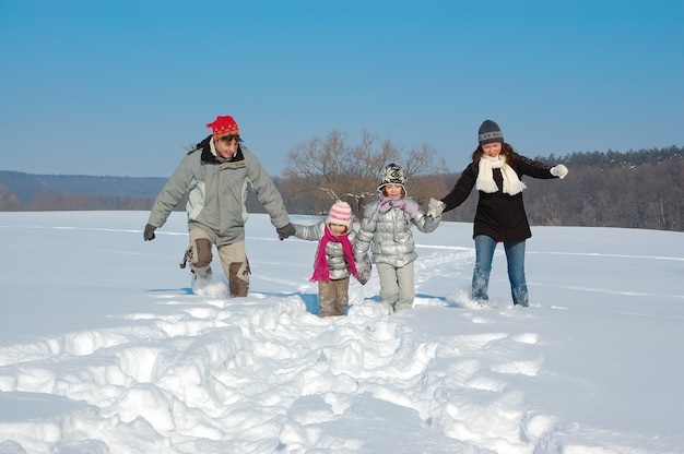 Счастливая семья гуляет зимой, веселится и играет со снегом на выходных в праздничные выходные