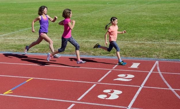 Семейный спорт и фитнес, счастливая мать и дети, бегущие по стадионной дорожке на свежем воздухе