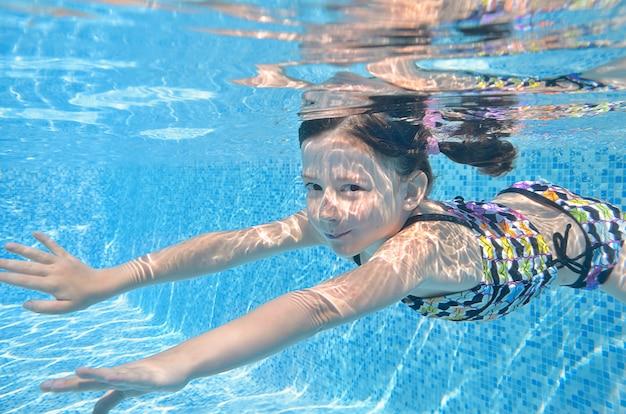 子供はプールで泳いで、幸せなアクティブな女の子がダイブし、家族での休暇に水、子供のフィットネス、スポーツを楽しんでいます