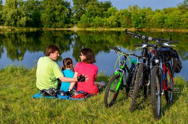 Семья на велосипедах на открытом воздухе, активные родители и ребенок, езда на велосипеде и отдыха возле красивой реки, фитнес-концепция