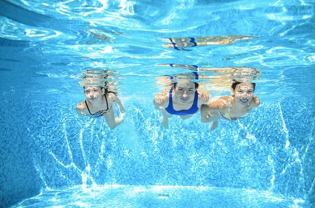 家族はプールで泳ぎ、アクティブな母親と子供たちはリゾートで夏休みに子供たちと水、フィットネス、スポーツの下で楽しんでいます