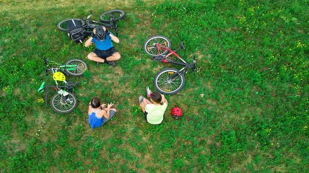 Семья катается на велосипеде на открытом воздухе с высоты птичьего полета, счастливые активные родители с ребенком веселятся и отдыхают на траве, семейные виды спорта и фитнес по выходным