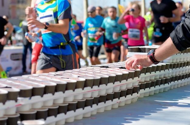 マラソンランニングレース、道路上のランナー、リフレッシュポイントでの水と等張性ドリンクのボランティア