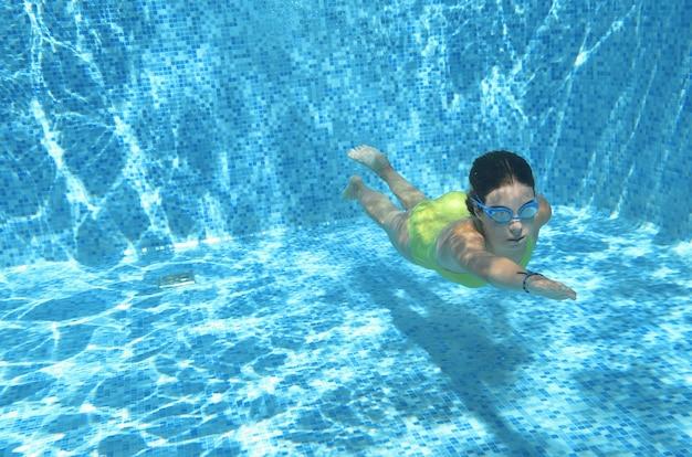 プールで水の下で泳いでいる若い女の子のスイマーと楽しい、水中ダイビング、家族での休暇、スポーツ、フィットネスの概念