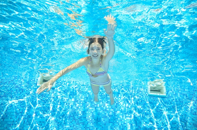 子供はスイミングプールで水中を泳ぎ、幸せなアクティブなティーンエイジャーの女の子がダイブし、リゾートで家族での休暇に水、子供のフィットネス、スポーツの下で楽しい