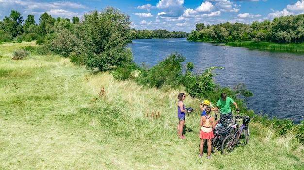 Семья на велосипедах на велосипеде на свежем воздухе, активные родители и дети на велосипедах, вид сверху счастливой семьи с детьми, отдыхающими возле красивой реки сверху, концепция спорта и фитнеса