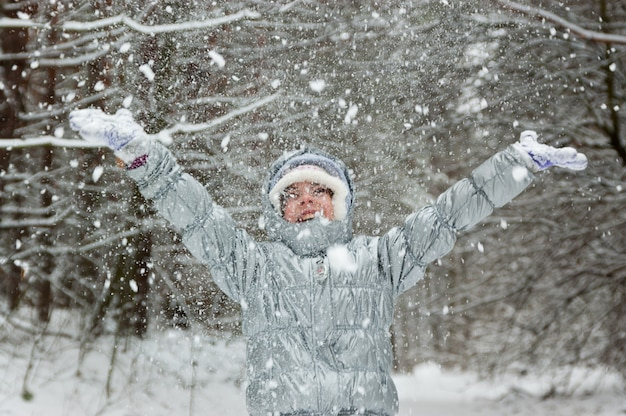 Счастливый активная девушка весело и бросали снег в зимнем лесу, улыбаясь, играя ребенка. малыш на зимних каникулах