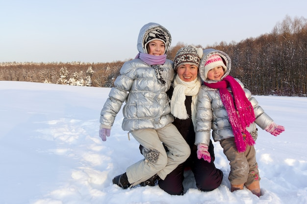 冬の雪の屋外で楽しんで幸せなアクティブな家族。母と子供たちの笑顔