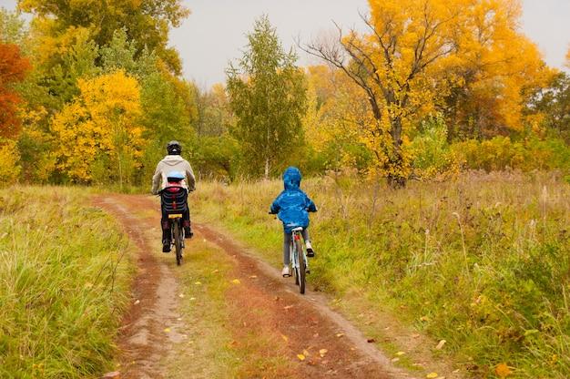 屋外サイクリング、公園で黄金の秋の家族。父と子供たちの自転車。ファミリースポーツ