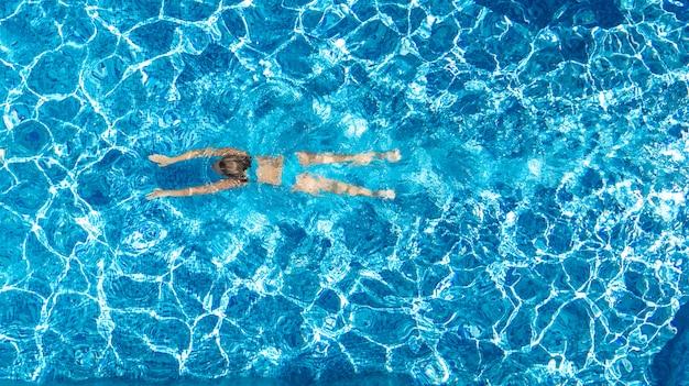 上からスイミングプール空中ドローンビューでアクティブな女の子、若い女性は青い水で泳ぐ