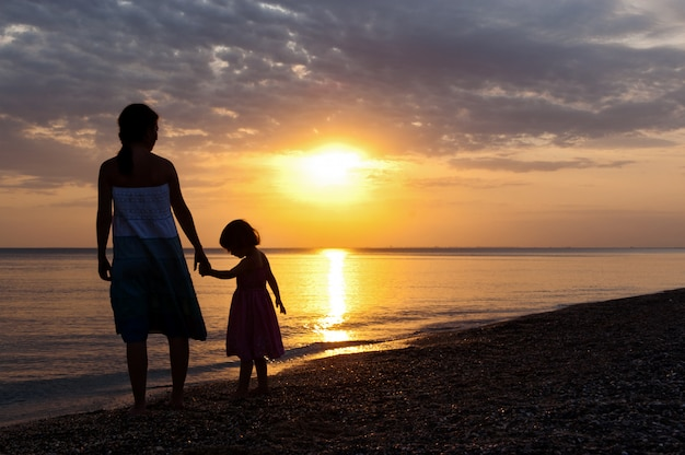 Мать и ребенок на пляж заката.