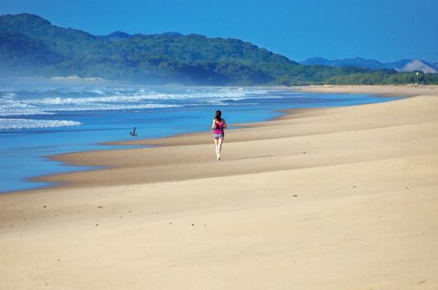 Женщина работает на пляже, красивая девушка бегун трусцой на открытом воздухе, обучение марафону, упражнения и фитнес-концепция