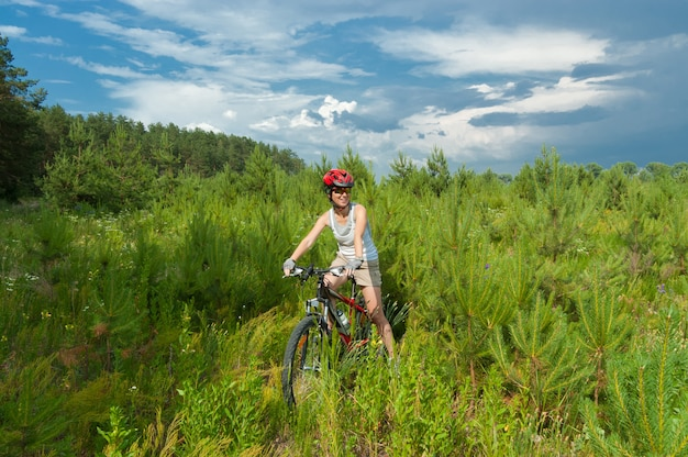 Женщина езда на велосипеде в лесу