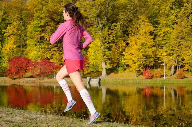 秋の公園、屋外でジョギング、マラソン、運動、フィットネスの概念のためのトレーニングで美しい少女ランナーで走っている女性