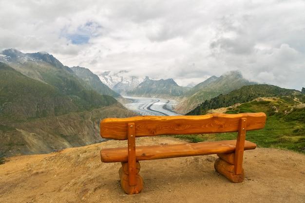 夏、スイスの山の視点で木製のベンチと美しい牧歌的なアルプスの風景