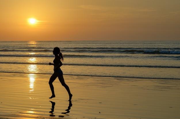 Силуэт бегуна женщины бежать на пляже захода солнца, фитнесе и концепции здорового образа жизни