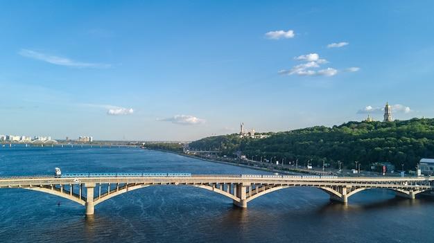 電車とドニエプル川の地下鉄鉄道橋の空中ドローンビュー
