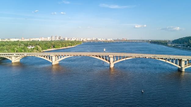 電車とドニエプル川の地下鉄鉄道橋の空中ドローンビュー。ウクライナキエフ市のスカイライン